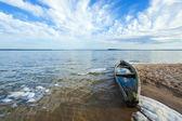 Old flooding boat on summer lake shore — Stock Photo