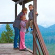 Family on wooden mountain cottage porch — Stock Photo