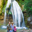 Family on summer waterfall background - Stock Photo