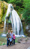 Family on summer waterfall background — Stockfoto