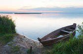 Sunset with old flooding boat on summer lake shore — Stock Photo