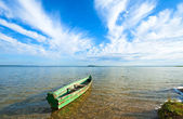 Boat on summer lake bank — Stock Photo