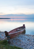 Sunset with boat near the summer lake shore — Stock Photo