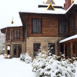Country wooden house and winter fir trees - Stock Photo