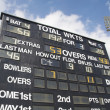 Cricket scoreboard and floodlight - Stock Photo