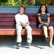 Royalty-Free Stock Photo: Boy and girl sitting on the bench.