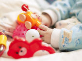 Hand with baby toys — Stock Photo