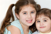 Cute Hispanic-American sisters pose and smile for a portrait. — Stock Photo