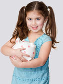 Cute little girl cradles a pink polka dotted piggybank in arms. — Stock Photo
