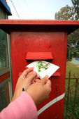 Backpacker send postcard to red post box — Stock Photo