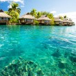 Over water bungalows with steps into green lagoon - Stock Photo