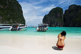 Girl photographing tropical beach with boats — Stock Photo