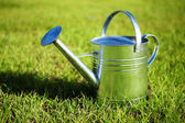 Shiny metal watering can in the grass — Stock Photo