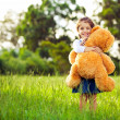Little cute girl standing in the grass holding teddy bear — Stock Photo