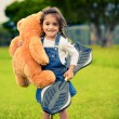 Cute girl standing in the grass holding teddy bear — Stockfoto