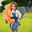 Cute girl standing in the grass holding teddy bear — Stock fotografie