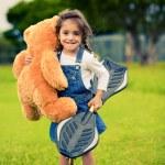roztomilá dívka stojící v trávě drží medvídek — Stock fotografie