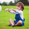Young girl sitting on a grass throwing ball — Foto de Stock