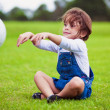 Young girl sitting on a grass throwing ball — Stockfoto