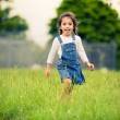 Happy girl walking in a green meadow — ストック写真