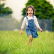 Happy girl walking in a green meadow — Stock fotografie