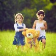 Two little girls in the grass with teddy bear — Stok fotoğraf