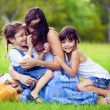 Mother and two daughters playing in grass — Stock Photo #4525901