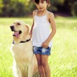 Girl standing in grass with golden retriever — Stock Photo