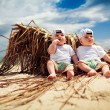 Identical twin boys relaxing on a beach - Stock Photo
