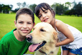 Young boy and girl hugging a golden retriever — Stok fotoğraf