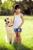 Ragazza in piedi in erba con golden retriever — Foto Stock