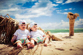 Identical twin boys relaxing on a beach — Stock Photo