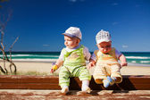 Two baby twin brother twins sitting on a beach jetty — Stok fotoğraf