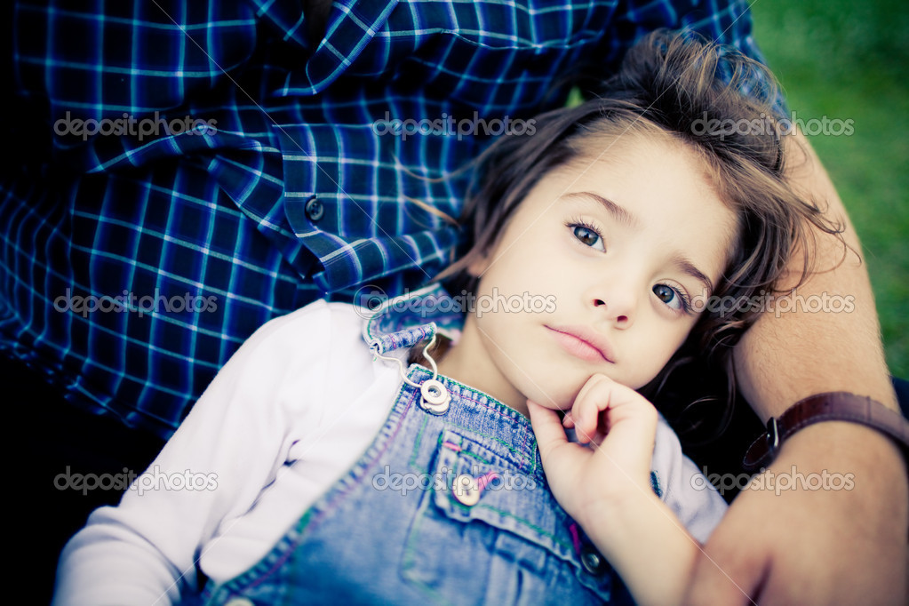 Gorgeous baby girl relaxing in father's lap outdoors — Stock Photo #4525823