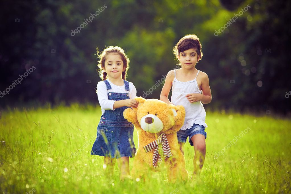 Two little girls in the tall grass with teddy bear — Stock Photo #4525876