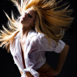 Beautiful blond female with flying hair dancing — Stock Photo #4728256