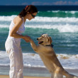 Young female dancing on a beach with a dog — Stock Photo #4728388