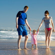 Young family with daughter on the beach — Stock Photo