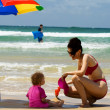 Mother and daughter playing on the beach — Stock Photo #4728454