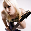 Young blonde female holding rock guitar — Stock Photo