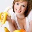 Stock Photo: Young beautiful female eating a bananna