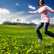 Young girl jumping on a meadow - Stock Photo