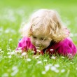 Little girl smelling flowers — Stock Photo #4728671