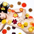 Young woman relaxing covered in flowers - Stock Photo