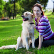 Young woman and golden retriever in the grass - Stock Photo