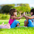 Two young smiling girls sitting in the grass — Stock Photo