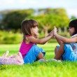 Stock Photo: Two young smiling girls sitting in the grass