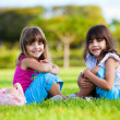 Two young smiling girls sitting in the grass - Stock Photo