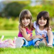 Two young smiling girls hugging in the grass - Stock Photo