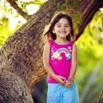 leende ung flicka stående på trädgrenar — Stockfoto